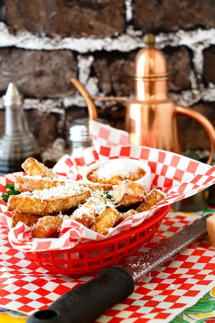 "Deep-fried cheesy polenta fries are very easy to make. The polenta itself is creamy and a bit smoky from bacon fat, and the fries have a crisp coating. Deep fried (or baked) and served with red pepper tomato dipping sauce/""ketchup,"" this is a comfort food recipe you won't want to miss. 