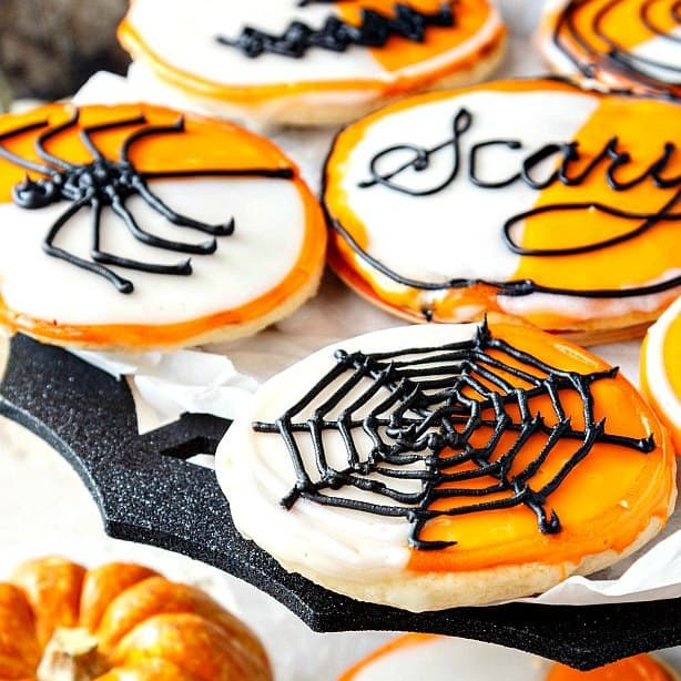 "tray of orange and white iced cookies with spider decorations. Text on one of them reads ""Scary."""