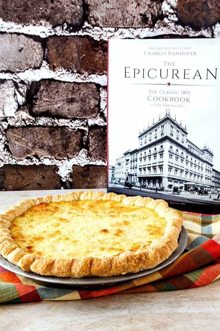 whole coconut custard pie in the tin with the cookbook it came from in the background. Text on Cookbook reads: The Epicurean The Classic 1893 Cookbook
