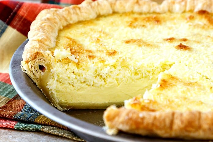 closeup of coconut custard pie with one slice cut from it. You can see the flaky layers in the cut pie crust