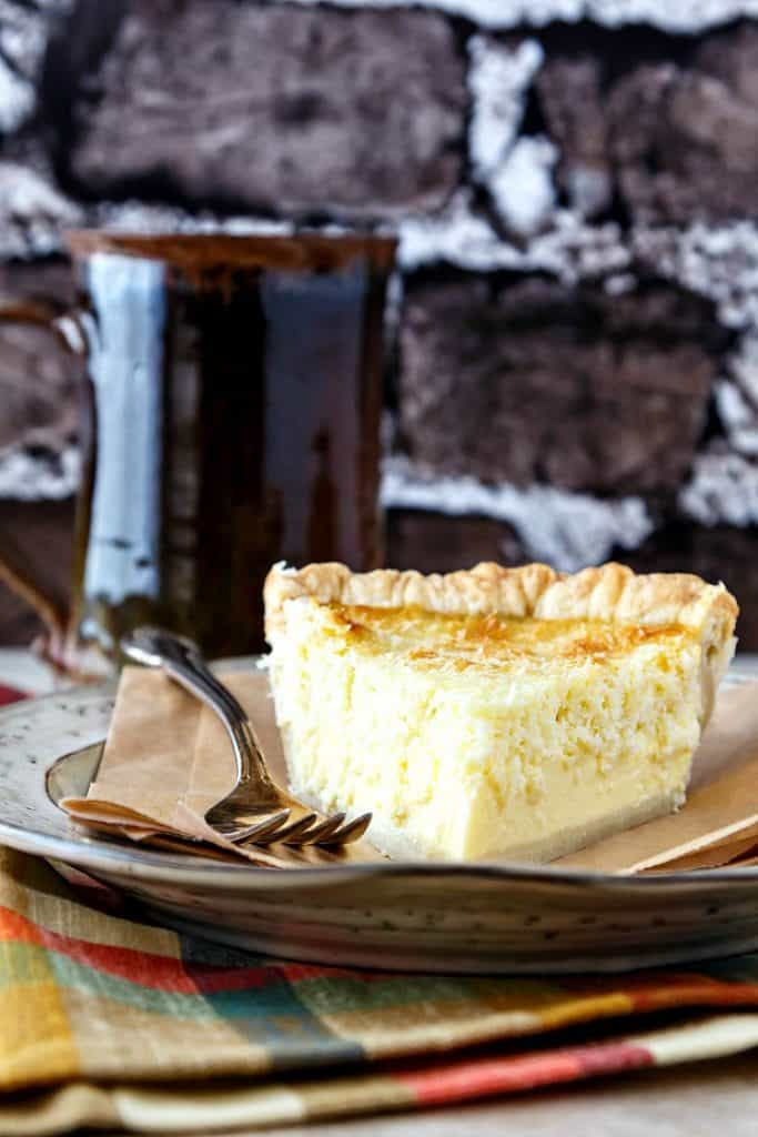 a slice of coconut custard pie on brown paper on a gray plate shot against a brick wall backdrop