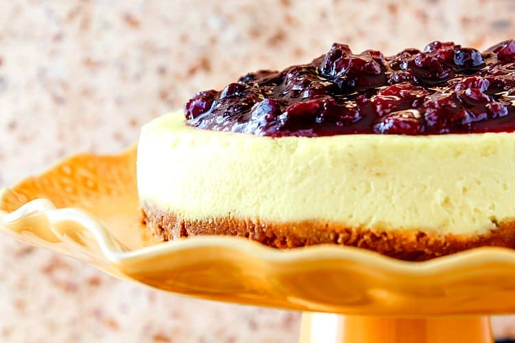 head on, close up view of the side of a cheesecake with fruit topping