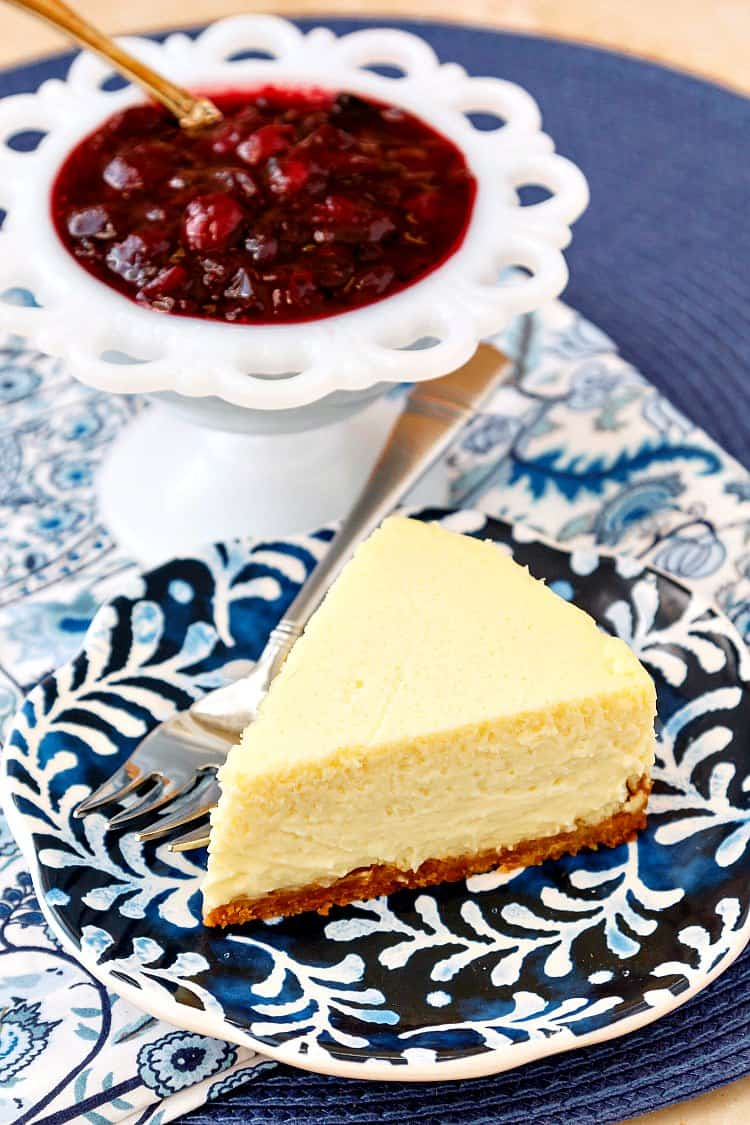 a slice of roasted corn cheesecake on a blue patterned plate with a white bowl of cranberry blueberry compote