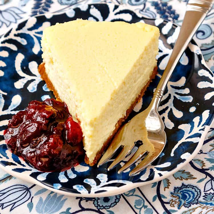 corn cheesecake slice on a blue and white plate with a fork and fruit compote