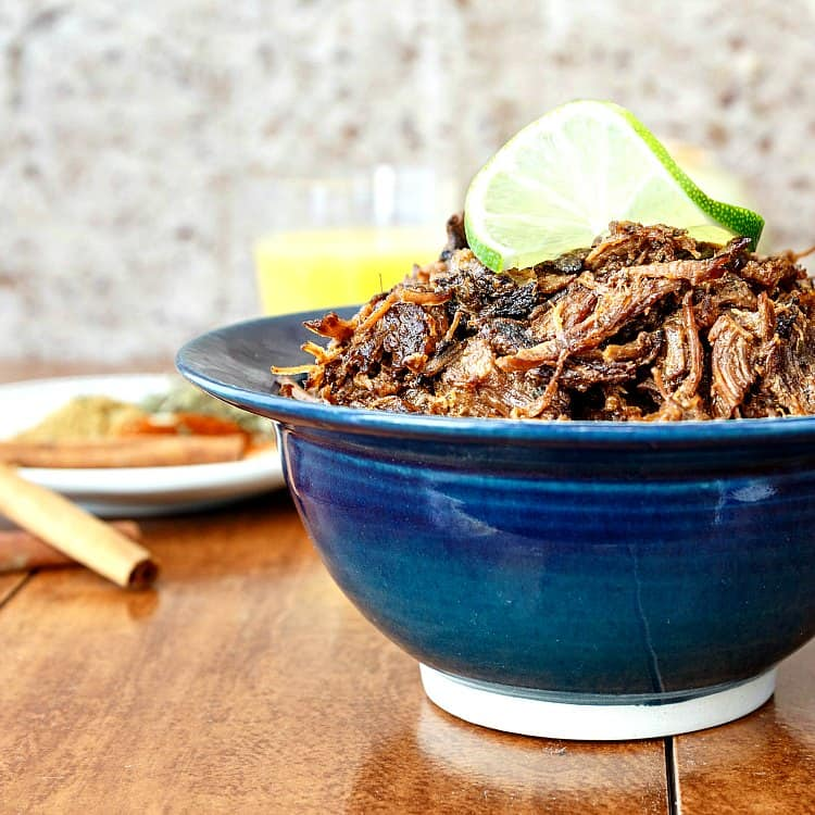 beef carnitas made in an instant pot and piled into a blue bowl