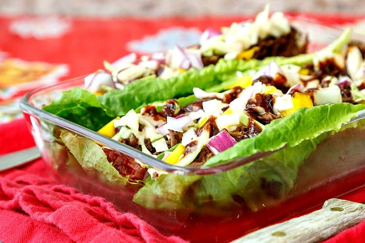 beef carnitas lettuce wraps in a rectangular glass dish on red cloth