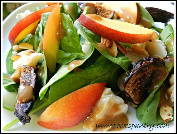a close up photo of spinach, nectarine, pecans, fig and cheese salad
