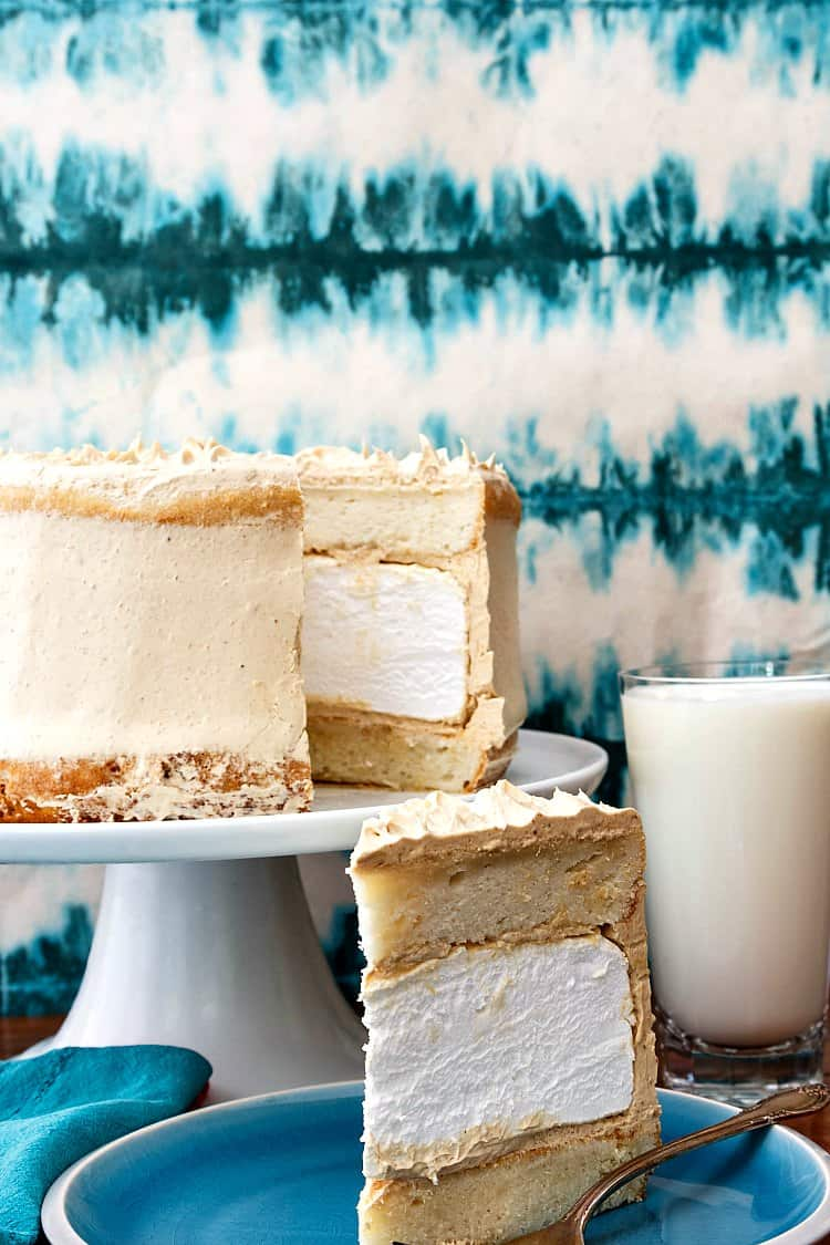 layer cake with white cake layers, homemade marshmallow, and peanut butter buttercream on a blue plate.