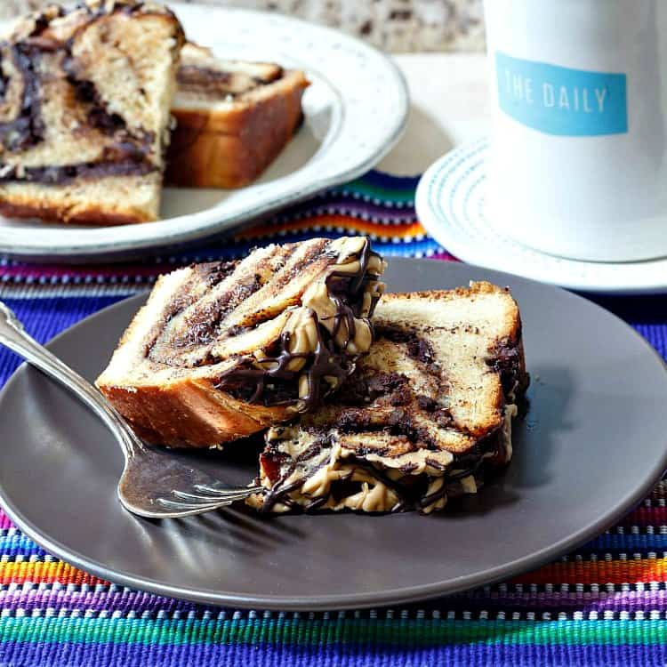 two slices of chocolate babka on a brown plate with a fork on it with another plate of babka in the background and a coffee cup