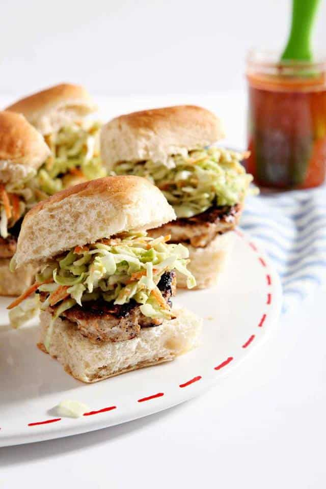four chicken burger sliders with cole slaw on a plate with a jar of barbecue sauce in the background.