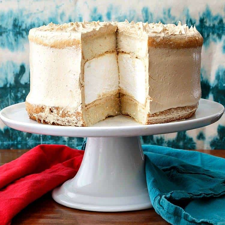 """whole layer cake cut to show the inside: two layers of white cake sandwiching a 2"""" layer of marshmallow all frosted in peanut butter frosting on a cake stand."""