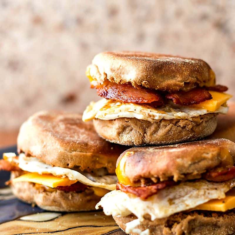 a stack of three whole wheat English muffins filled with fried egg, cheese, and bacon.