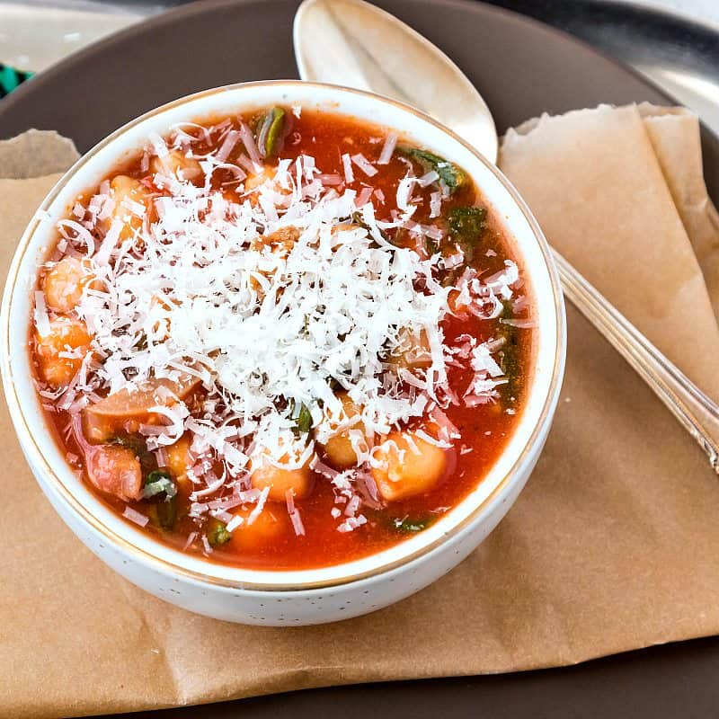 close up of a bowl of red-orange soup with chickpeas with Parmesan cheese shaved on the top.