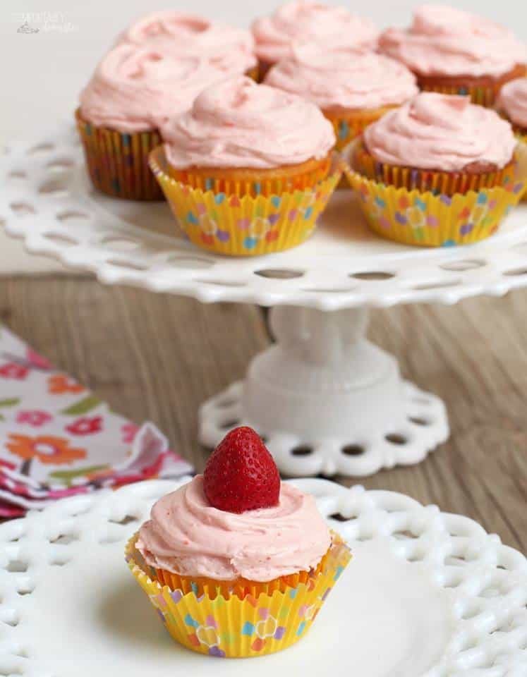 one cupcake with pink frosting and a strawberry on top on a white plate with a footed platter of more pink-frosted cupcakes in the background