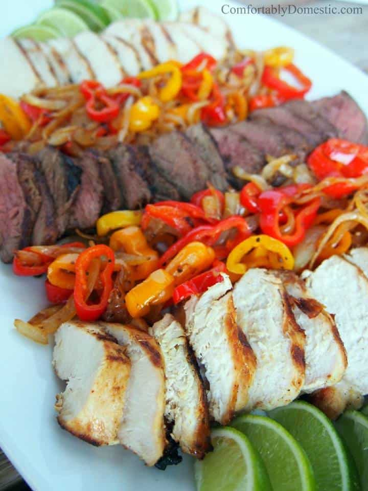 platter with grilled chicken and steak, onions and sweet peppers with lime slices