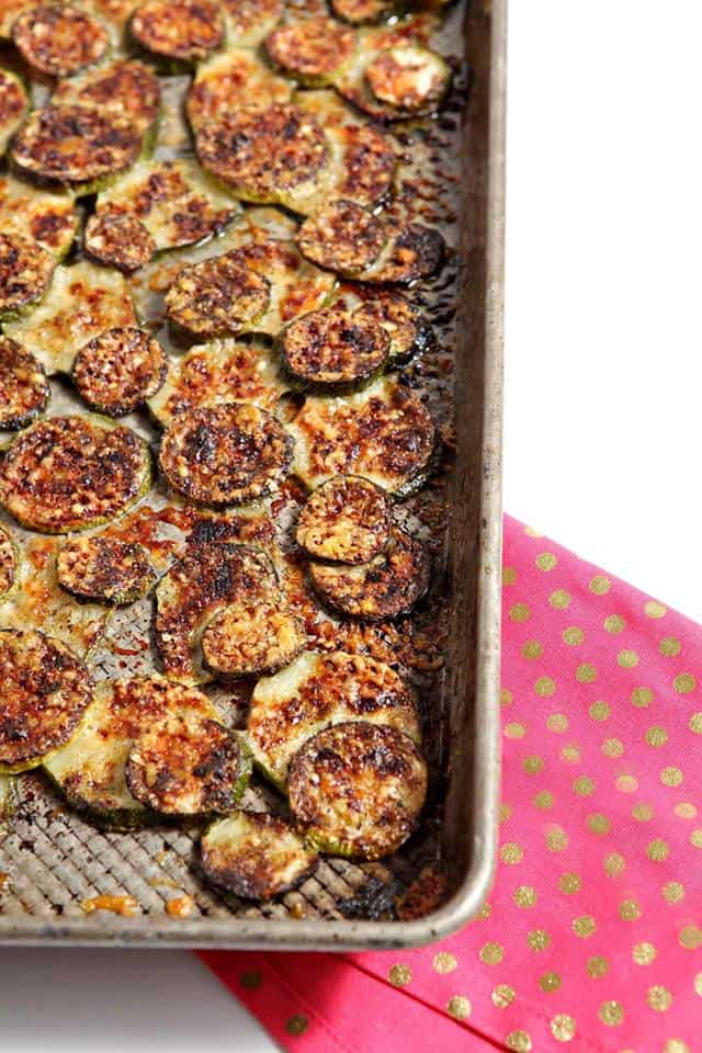 close up of a portion of a tray of broiled zucchini with crisp melted cheese on top
