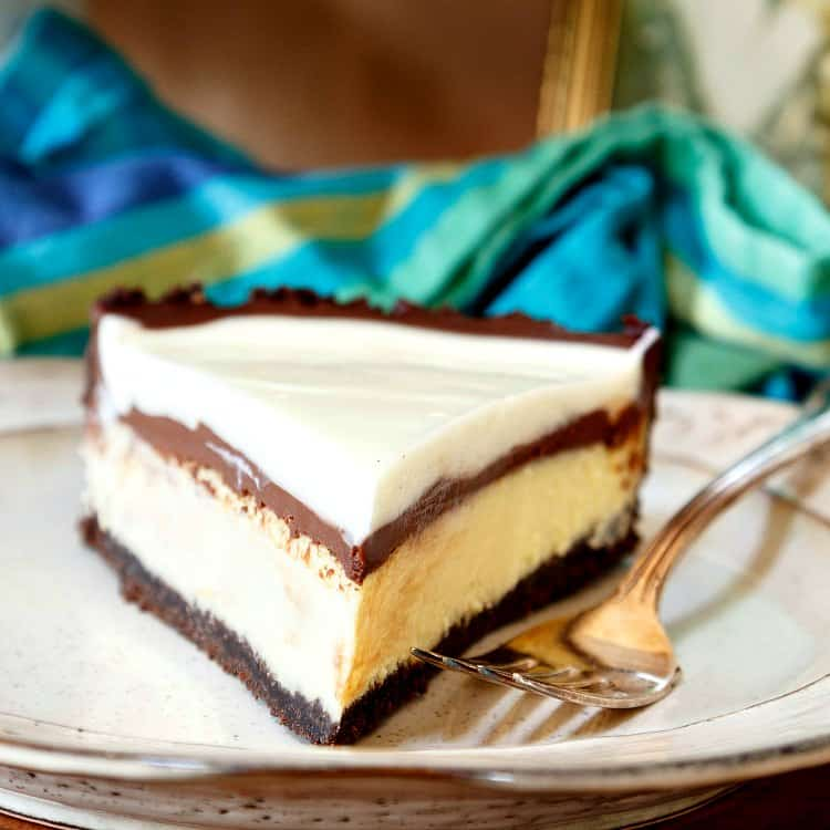 close up shot of a slice of chocolate cheese pie, head on, on a plate with a blue striped napkin in the background