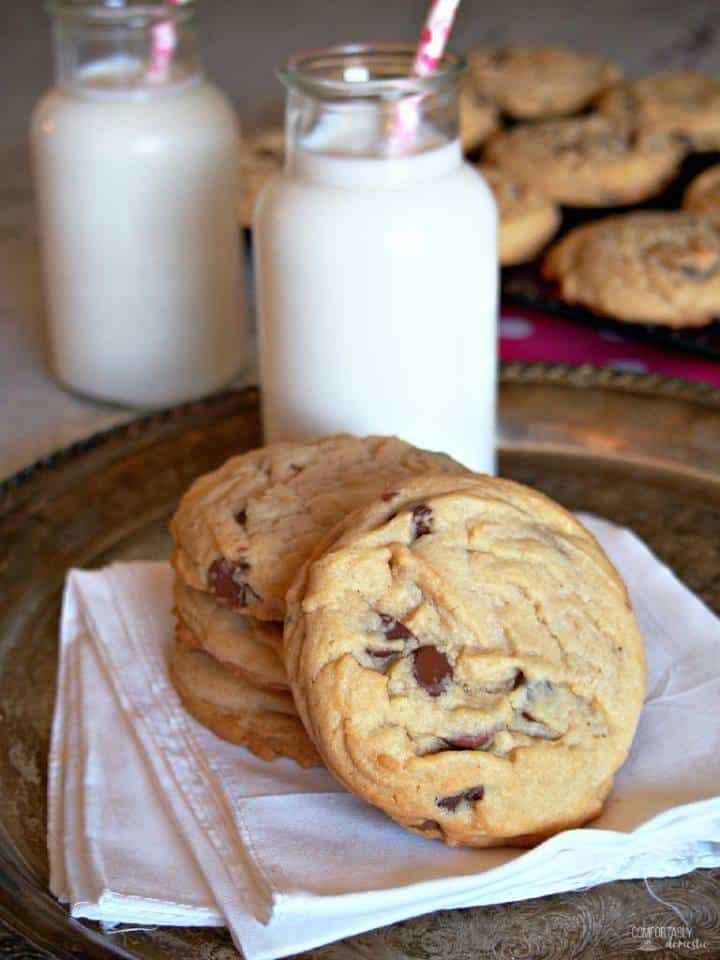4 large chocolate chip cookies on a folded white napkin with two small bottles of milk and a tray of more cookies in the background