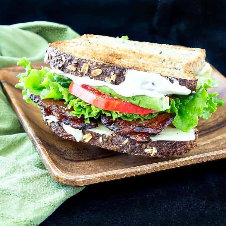 BLT sandwich on grain bread on a wooden plate with a green napkin
