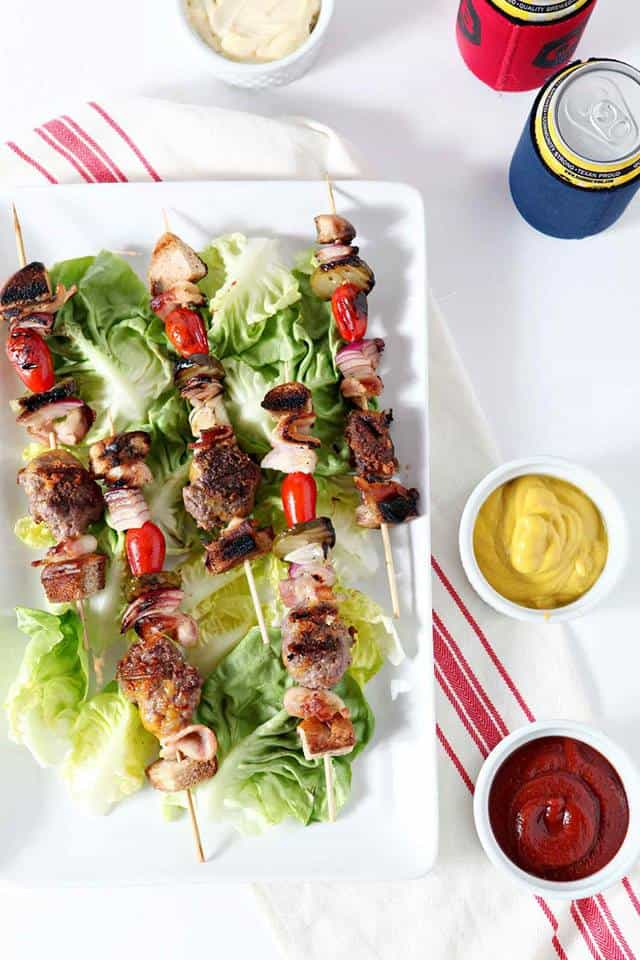 overhead shot of ground beef kebabs on a bed of lettuce on a white platter with ketchup and mustard on the side