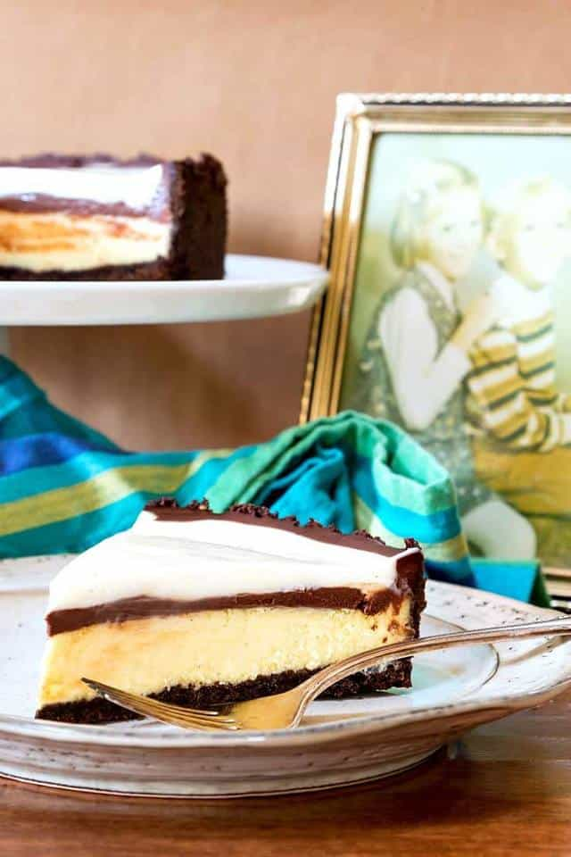 close up shot of a slice of pie with a cheesecake layer, a thin layer of fudge sauce, and sweetened sour cream topping