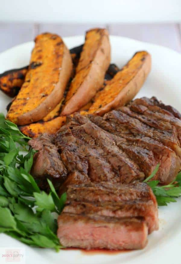 close up of plated, thickly sliced steak and grilled sweet potato wedges on a bed of Italian parsley.