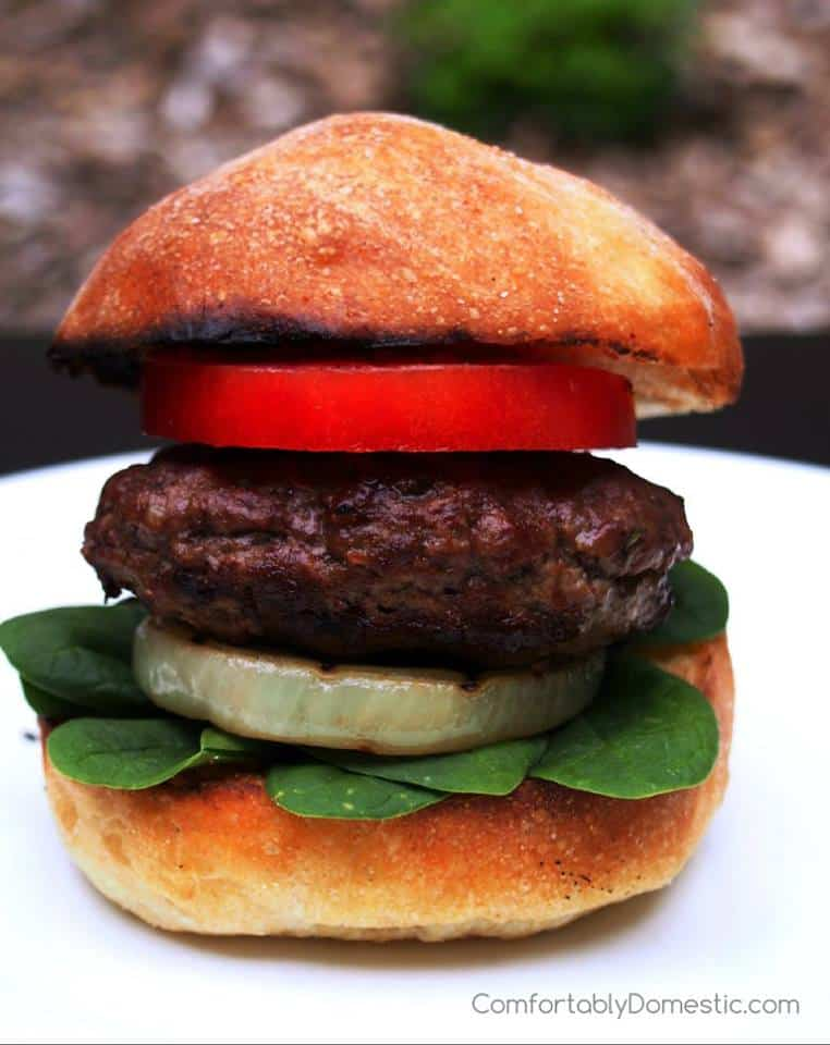 close up of a thick lamb burger on grilled onion and topped with a thick slice of tomato