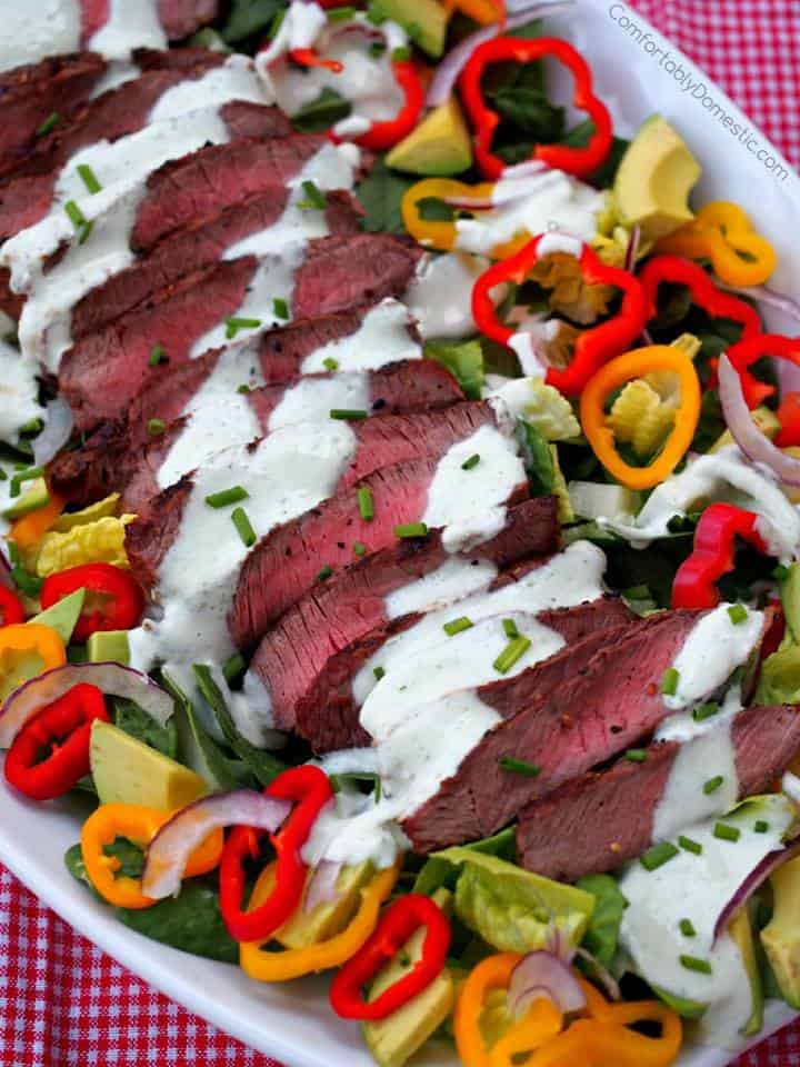 large platter of salad greens and vegetables topped with sliced medium rare steak and drizzled with a white dressing