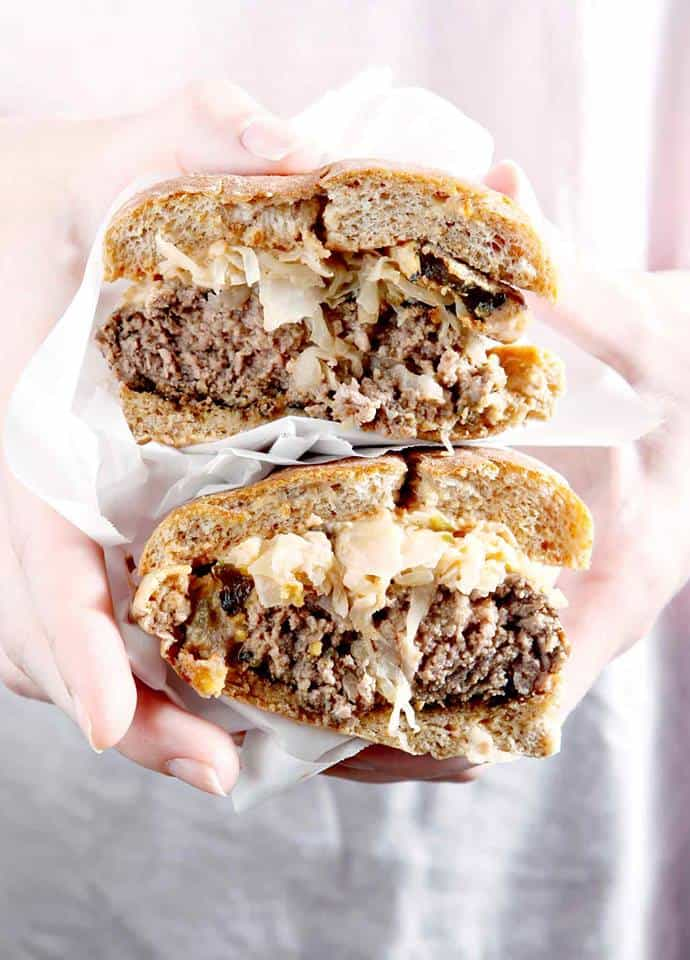 hands holding two halves of a cut burger stacked on top of each other topped with sauerkraut and a creamy sauce