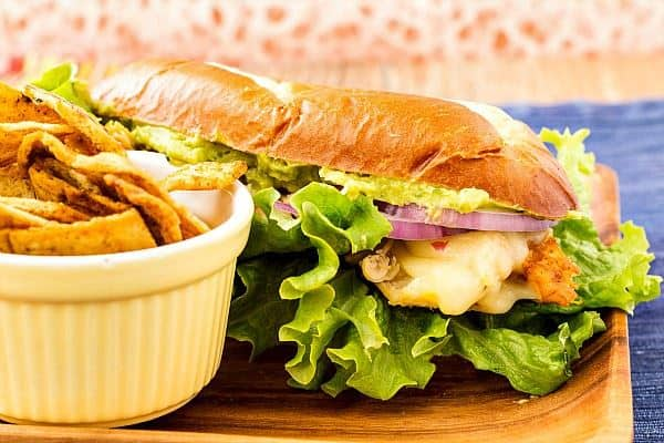 a sandwich of chicken, guacamole, red onions and cheese on a sub roll with a ramekin of corn chips
