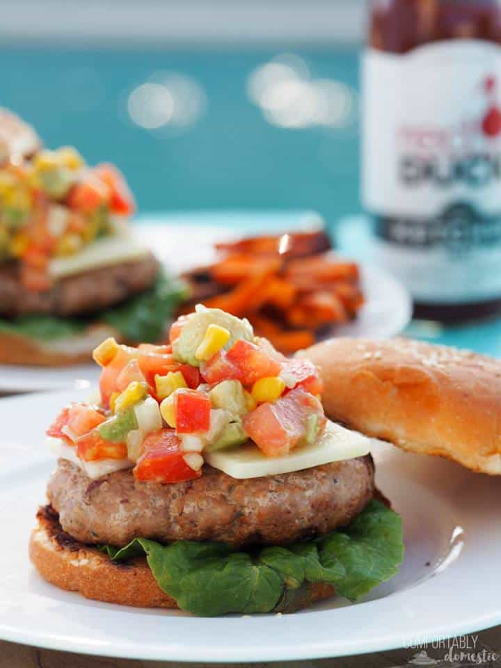 Open-faced plated turkey burger with corn and avocado salad on a bun with lettuce.