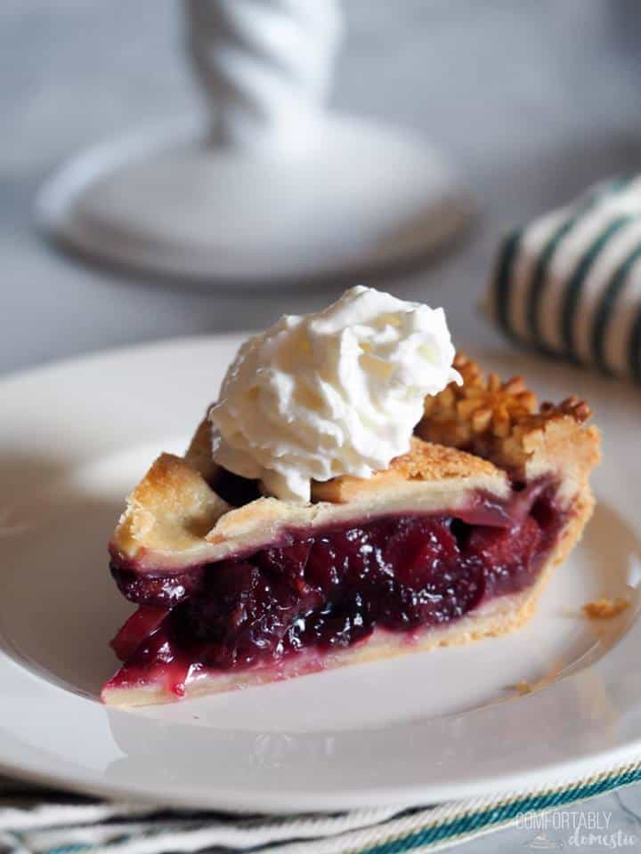 closeup of a slice of double crust berry pie topped with whipped cream