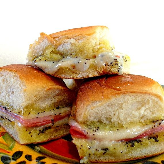 close up of three rolls layered with ham and Swiss cheese with poppy seed spread