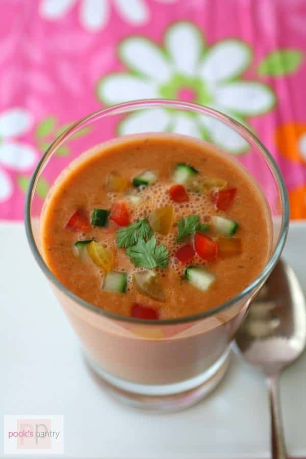 closeup of a clear glass of chilled soup with diced peppers and cucumbers for garnish with a pink and white floral background
