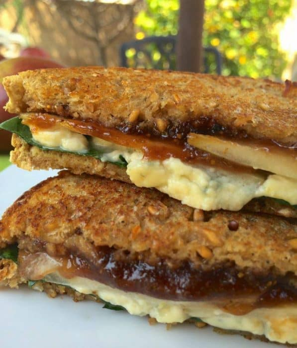 close up of a two toasted sandwich halves stacked on top of each other with white cheese, fig spread and sliced pears