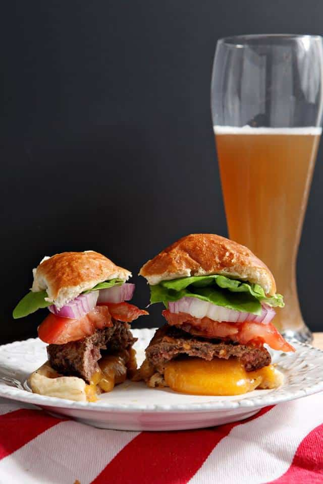 a plated hamburger topped with tomato, onion and lettuce cut in half on a plate with a pilsner glass of beer in the background