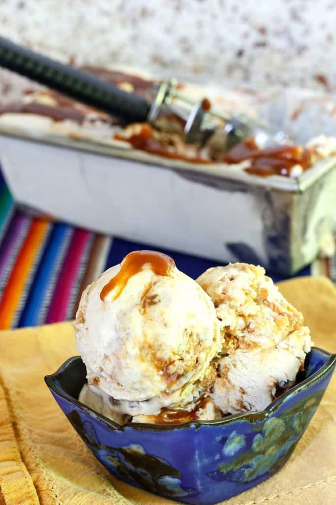 a blue bowl of ice cream with caramel swirls and bits of cinnamon roll with the container of ice cream in the background