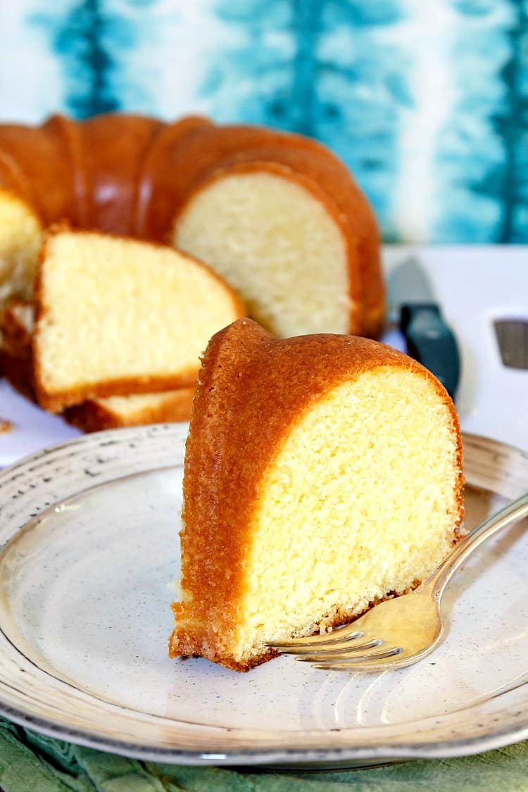 A sliced of buttermilk pound cake on a plate with the cake and two slices in the background
