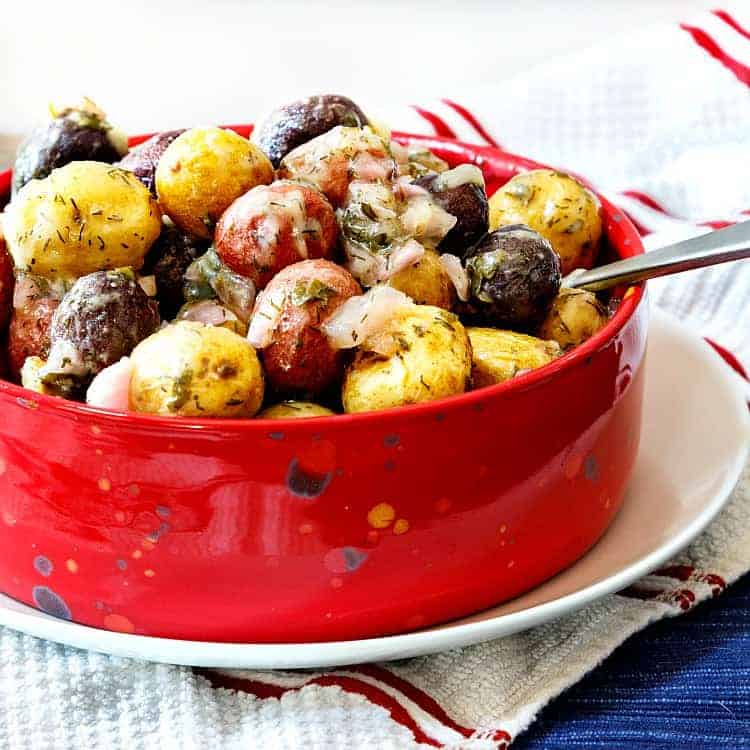 close up shot of a red bowl of potato salad made with red, white and blue baby potatoes on a white plate with a spoon in it