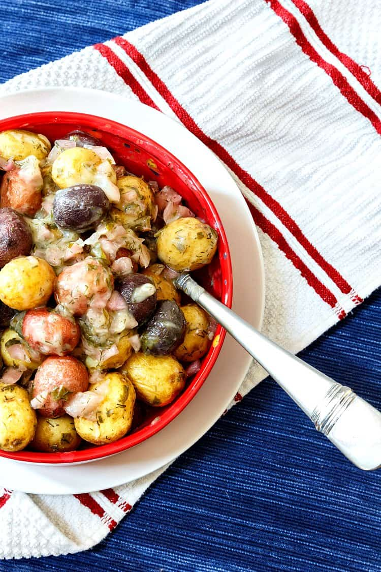 overhead shot of no mayo potato salad made with whole baby red, white, and blue potatoes in a red bowl on a white plate with a blue placemat as the background