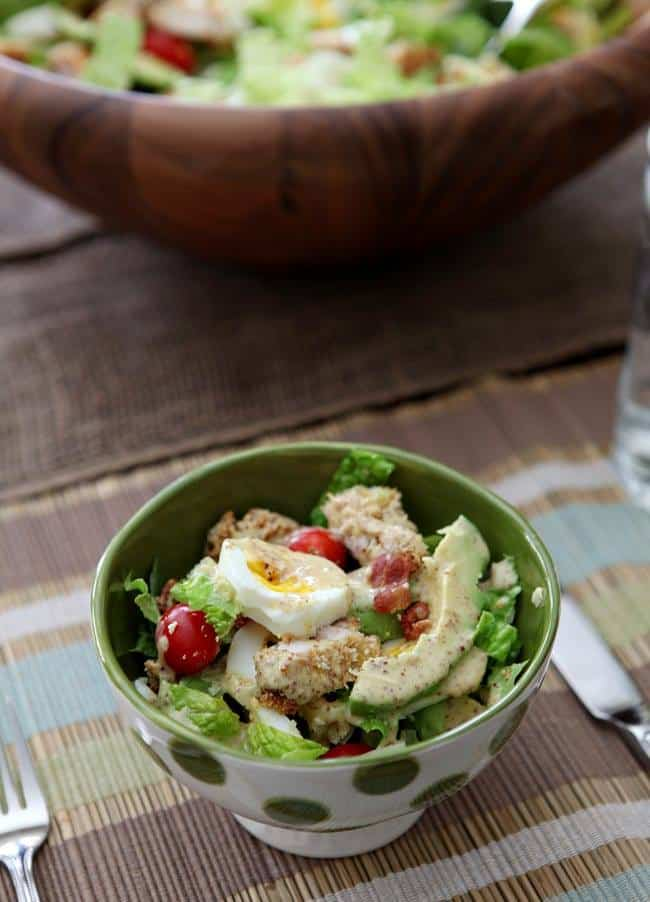 polka dotted dish of salad greens with chicken, hard boiled egg, tomato, avocado