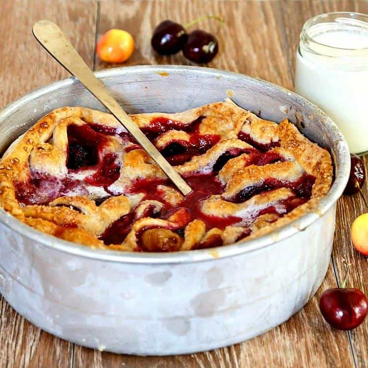 photo of red fruit dessert topped with browned pastry in a round metal pan.