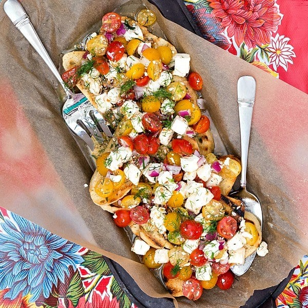 overhead shot of a tray full of toasted bread with yellow and red cherry tomatoes and fresh mozzarella piled on top