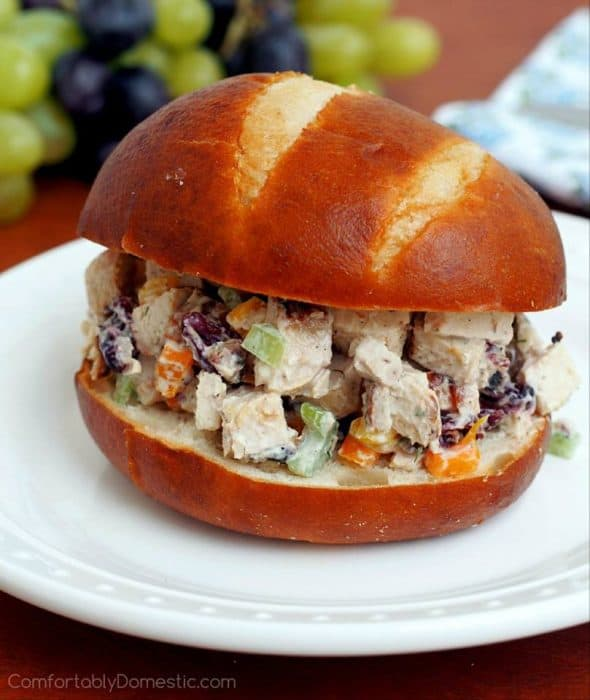 chicken salad sandwich on a bun on a white plate with grapes in the background
