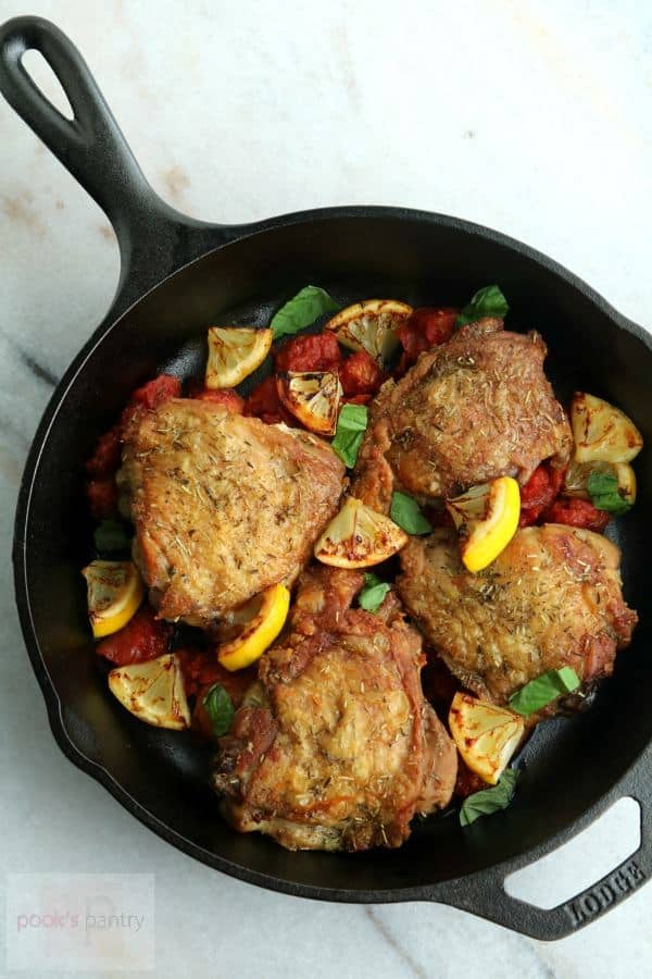 overhead shot of 4 chicken thighs on a bed of lemon slices and tomatoes in a cast iron skillet