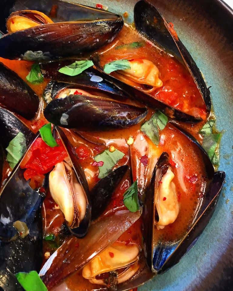 a close up of open mussels sprinkled with green herbs in a rich orange-red sauce