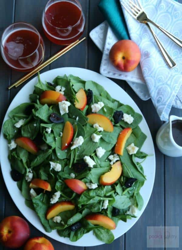 overhead shot of a platter of spinach with sliced nectarines and blue cheese crumbles