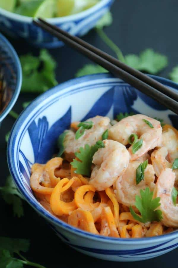 close up of a white and blue bowl with spiralized sweet potatoes and shrimp with cilantro