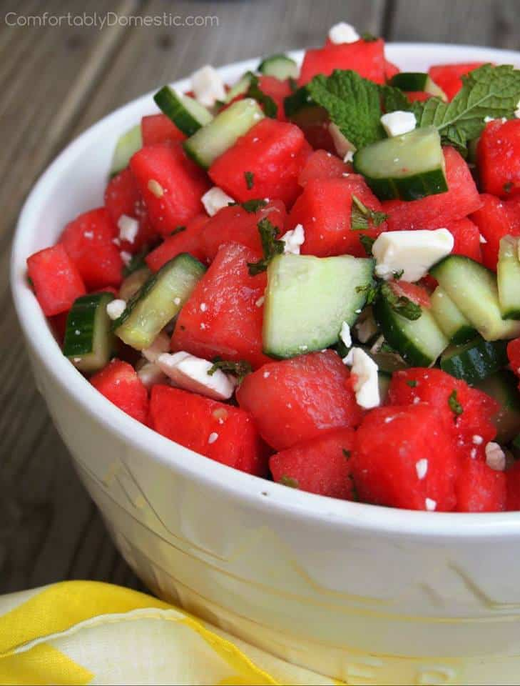 bowls containing a salad of watermelon chunks, cucumber slices, feta cheese and mint