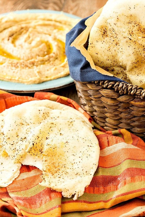 A large piece of pita bread, torn, on an orange striped napkin with a basket of pita in the midground and a plate with hummus in the background